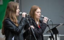 Photo of girls singing on stage at Croeso Swansea